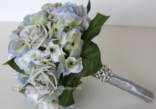 Silk wedding flowers comprised of blue hydrangeas and roses