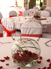 Red rose low centerpiece in goldfish bowl