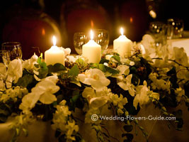 reception flowers on a top table with candles
